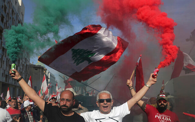 Anti-government protesters wave Lebanese national flags during a civil parade at the in downtown Beirut, Lebanon, November 22, 2019. (AP Photo/Hassan Ammar)