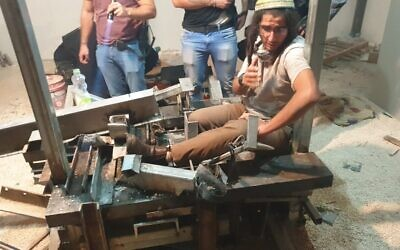 Neria Zarog attaches himself to a saw machine in Yitzhar to avoid arrest for violating an administrative order on November 10, 2019. (Honenu)