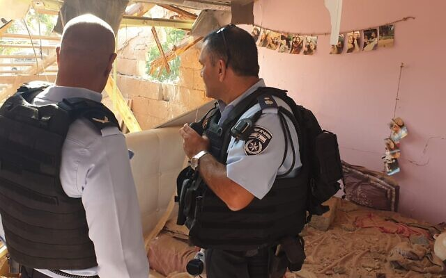 Police officers inspect the damage caused by a rocket fired from the Gaza Strip that struck a home in the Israeli town of Netivot on November 12, 2019. (Israel Police)
