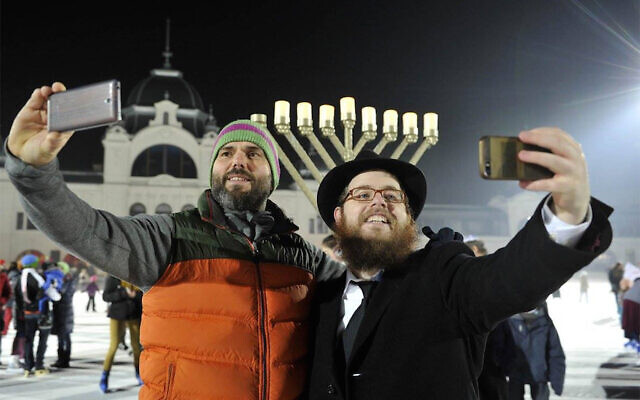 Rabbi Slomo Koves, right, and a participant at Chabad Hungary's 2015 Hanukkah on Ice event at Budapest's City Park Ice Rink, December 6, 2015. (Courtesy of EMIH via JTA/ File)