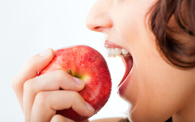 An illustrative image of a woman biting into an apple (kzenon; iStock by Getty Images)