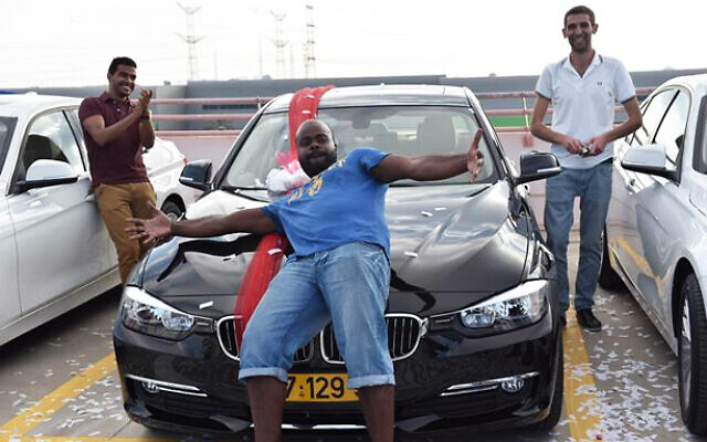 Oron Montgomery (center) received a BMW as a reward for being one of Yukom Communications top-earning employees in June 2015. Montgomery is one of 15 employees and executives of Yukom Communications indicted by the US Department of Justice in  an indictment dated September 25, 2019 and unsealed November 8, 2019. (Photo: Facebook)