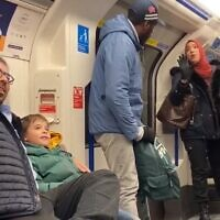 A Muslim woman (R) is seen trying to stop a man (C) from shouting anti-Semitic abuse at Jewish family with small children on the London Underground on November 22, 2109 (Screencapture/Twitter)
