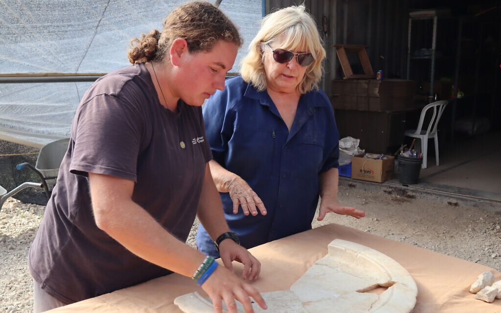 IAA archaeologist Dr. Tali Erickson-Gini (right) examines a marble tray from the altar area of the Byzantine church near Ashkelon. (Anat Rasiuk, Israel Antiquities Authority)