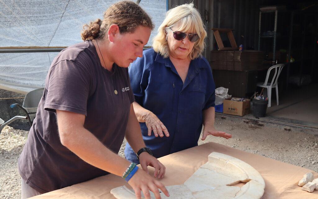IAA archaeologist Dr. Tali Erickson-Gini (right) examines a marble tray from the altar area of the Byzantine church near Ashkelon. (Anat Rasiuk, Israel Antiquities Authority)