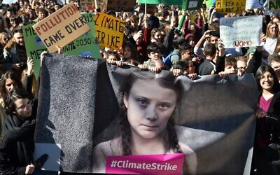 People and students hold placards and a banner showing 16-year-old Swedish political activist Greta Thunberg, who seeks to stop global warming and climate change, as they take part in a protest against global warming in central Rome on March 15, 2019. (Andreas Solaro/AFP)