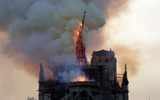 The steeple and spire of the landmark Notre-Dame Cathedral collapses as the cathedral is engulfed in flames in central Paris on April 15, 2019. (Photo by Geoffroy VAN DER HASSELT / AFP)