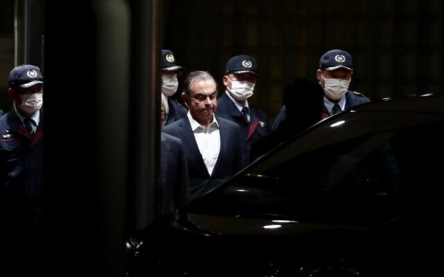 Former Nissan chairman Carlos Ghosn (C) is escorted as he walks out of the Tokyo Detention House following his release on bail in Tokyo on April 25, 2019. (Behrouz MEHRI / AFP)