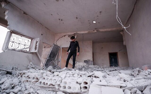 A Syrian youth walks through rubble and debris in a building that was damaged by a reported government forces airstrike in the village of al-Haraki in the northwestern Idlib province on December 1, 2019. (Omar HAJ KADOUR / AFP)