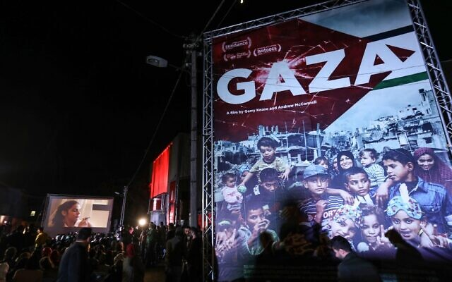 Palestinians watch a film during the opening ceremony of the Red Carpet Human Rights Film Festival, in front of the abandoned Cinema Amer building in Gaza City, December 4, 2019. (Photo by MAHMUD HAMS / AFP)