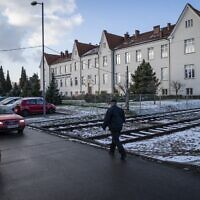 A man walks by the State High School of Oswiecim, located in what used to be SS troops's residential building, in Oswiecim, Poland, on December 3, 2019. (Photo by Wojtek RADWANSKI / AFP)