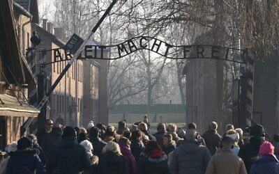 """Visitors enter through the main gate with the inscription """"Arbeit macht frei"""" (literally in English: """"work makes (one) free"""") at the entrance to the Auschwitz German Nazi death camp ahead of German Chancellor Angela Merkel's landmark visit in Oswiecim, Poland, on December 5, 2019. (JANEK SKARZYNSKI / AFP)"""