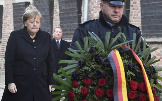 German Chancellor Angela Merkel lays a wreath at the Death Wall during her visit at the former German Nazi death camp Auschwitz-Birkenau in Oswiecim, Poland on December 6, 2019. (John Macdougall/AFP)