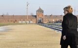 German Chancellor Angela Merkel walks in front of the main railway entrance to Birkenau as she visits the former German Nazi death camp Auschwitz-Birkenau in Oswiecim, Poland on December 6, 2019. (John MacDougall/AFP)