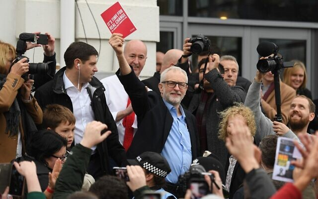 Britain's opposition Labour party leader Jeremy Corbyn holds his party's manifesto book aloft as he addresses a crowd outside the venue of a general election campaign event in Swansea, south Wales on December 7, 2019. (Daniel Leal-Olivas/AFP)