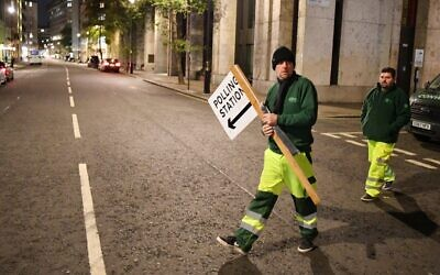 Council workers put up signs in central London as polling stations open for a general election in London on December 12, 2019. (DANIEL LEAL-OLIVAS / AFP)