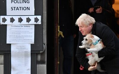 Britain's Prime Minister Boris Johnson poses with his dog Dilyn as he leaves from a polling station in central London on December 12, 2019, as Britain holds a general election. (DANIEL LEAL-OLIVAS / AFP)