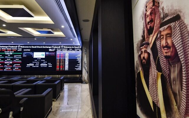 This picture from December 12, 2019, shows (L) a view of the exchange board at the stock market (Tadawul) in Riyadh displaying Aramco shares on the second day of their trading, along with a poster depicting Saudi Arabia's founder King Abdulaziz ibn Saud (C), his son and current King Salman bin Abdulaziz (R), and the latter's son Crown Prince Mohammed bin Salman. (Fayez Nureldine/AFP)