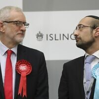 Britain's opposition Labour Party leader Jeremy Corbyn (L) exchanges a glance with the Brexit Party candidate Yosef David (R) as they stand on the stage waiting for the result from the election race for the constituency of Islington North at the count centre in Islington, north London, on December 13, 2019 (ISABEL INFANTES / AFP)