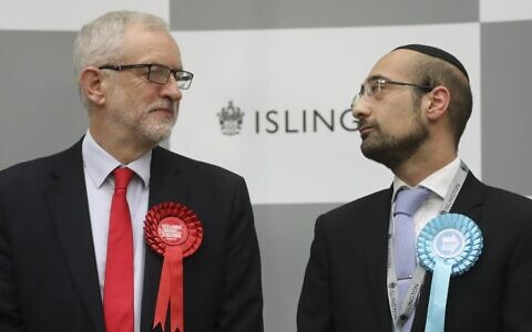 Britain's opposition Labour Party leader Jeremy Corbyn (L) exchanges a glance with the Brexit Party candidate Yosef David (R) as they stand on the stage waiting for the result from the election race for the constituency of Islington North at the count centre in Islington, north London, on December 13, 2019 (Isabel Infantes/AFP)