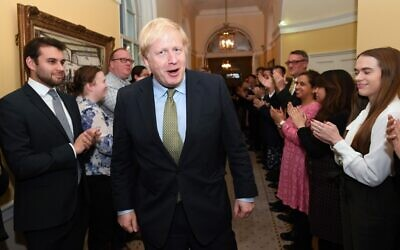 Britain's Prime Minister and Conservative Party leader Boris Johnson is greeted by staff as he arrives back at 10 Downing Street in central London on December 13, 2019, following an audience with Britain's Queen Elizabeth II at Buckingham Palace, where she invited him to become prime minister and form a new government. (Stefan Rousseau/POOL/AFP)