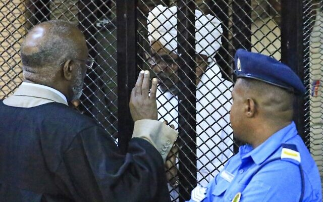 Sudan's deposed president Omar al-Bashir sits in a defendant's cage during his corruption trial at a court in Khartoum on December 14, 2019. (AFP)