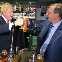 Britain's Prime Minister Boris Johnson gestures after pulling a pint with newly elected Conservative party MP for Sedgefield, Paul Howell, at Sedgefield Cricket Club in County Durham, north east England on December 14, 2019, following his Conservative party's general election victory.  (Photo by Lindsey Parnaby / POOL / AFP)