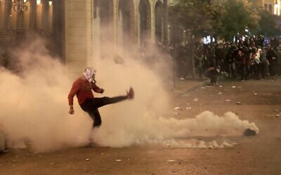 A Lebanese demonstrator kicks back a tear-gas canister during clashes with riot police in the capital Beirut on December 15, 2019. (ANWAR AMRO / AFP)