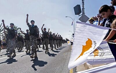 In this photo from October 1, 2019, Cypriots wave the flags of Cyprus and Greece during a military parade marking the 59th anniversary of Cyprus' independence from British colonial rule, in the capital Nicosia. (Iakovos Hatzistavrou/AFP)