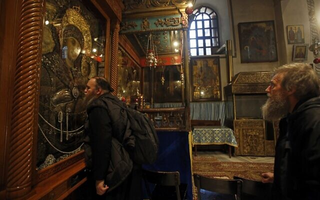 A Christian pilgrim kisses an icon of the Virgin Mary in the Church of the Nativity, the site where Christians believe Jesus was born, in the West Bank city of Bethlehem on December 18, 2019. (Musa Al Shaer/AFP)