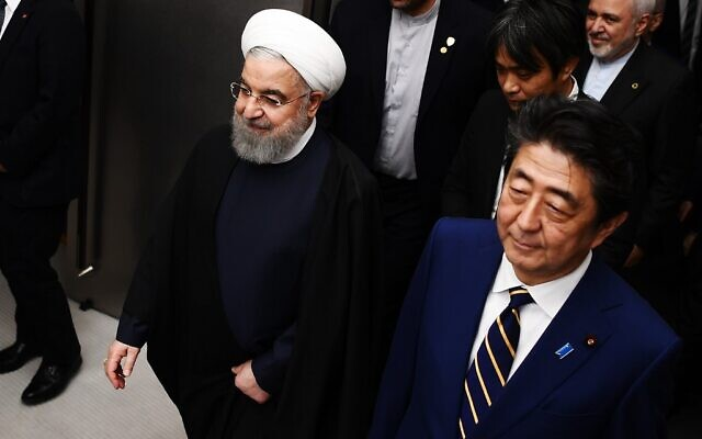 Iranian President Hassan Rouhani (L) walks with Japanese Prime Minister Shinzo Abe (R) to a meeting room at the prime minister's office in Tokyo on December 20, 2019. (Charly  Triballeau/Pool/AFP)