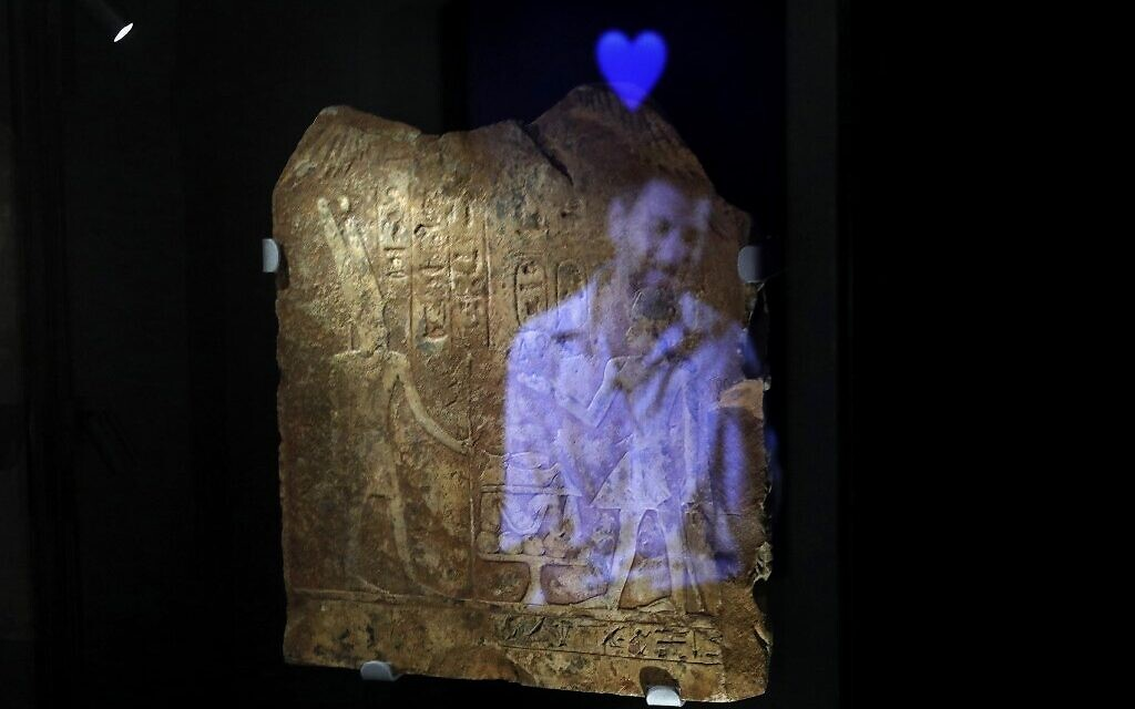 "A video installation shows the image of a man with the emoji of a blue hart reflected on an ancient Egyptian plaque engraved with Hieroglyphs, at the exhibition ""Emoglyphs: Picture-Writing from Hieroglyphs to the Emoji"" at the Israel Museum in Jerusalem, on December 19, 2019. (MENAHEM KAHANA / AFP)"