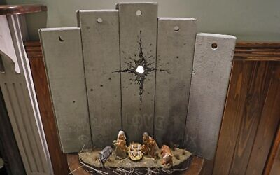 """A new Christmas-themed artwork dubbed the """"Scar of Bethlehem"""" by British street artist Banksy is displayed at his Walled-Off Hotel in Bethlehem in the West Bank on December 20, 2019. (Ahmad Gharabli/AFP)"""