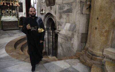 A Christian Armenian priest blesses the Church of the Nativity in the biblical West Bank city of Bethlehem on December 23, 2019. (AHMAD GHARABLI/AFP)