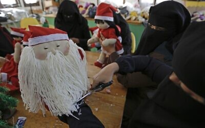 A Palestinian artisan puts the final touches on a Christmas toy at Zeina Association and Cooperative for Handicraft in Beit Hanoun in the northern Gaza Strip on December 24, 2019. (MOHAMMED ABED / AFP)