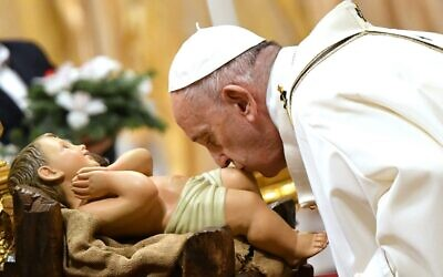Pope Francis kisses a figurine of baby Jesus during a mass on Christmas eve at St Peter's basilica in the Vatican, on December 24, 2019. (Alberto PIZZOLI AFP)