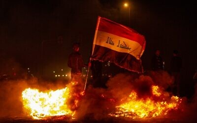An Iraqi anti-government protester holds a national flag as he stands by a fire at a makeshift roadblock in the southern city of Basra late on December 25, 2019. (Photo by Hussein FALEH / AFP)