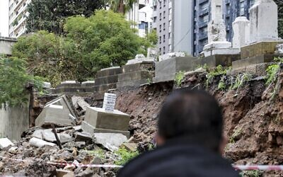 People look at graves damaged during bad weather in a winter storm at the Jewish cemetery in the Lebanese capital Beirut on December 26, 2019. (Anwar Amro/AFP)