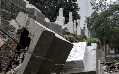 This picture taken on December 26, 2019, shows graves damaged during bad weather in a winter storm at the Jewish cemetery in the Lebanese capital Beirut. (Anwar Amro/AFP)
