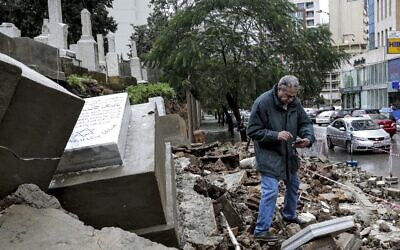 A man inspects graves damaged during bad weather in a winter storm at the Jewish cemetery in the Lebanese capital Beirut on December 26, 2019. (Anwar Amro/AFP)