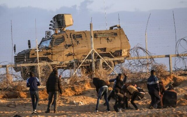 Palestinian rioters throw stones towards Israeli forces at the Israel-Gaza border, east of Rafah in the southern Gaza Strip, on December 27, 2019. (Photo by SAID KHATIB / AFP)