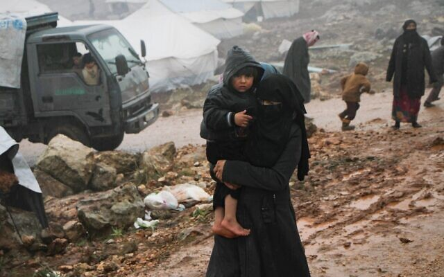 A Syrian woman who fled from government forces' advance on Maaret al-Numan in the south of the Idlib prvoince, carries a child at a camp for displaced people near the village of Harbnoush on December 27, 2019. (Aref TAMMAWI/AFP)
