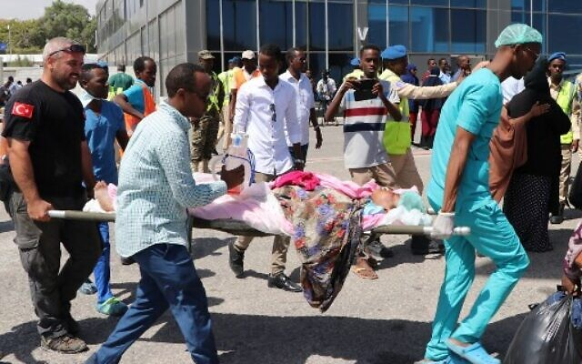 Rescue workers from Somalia and Turkey carry a woman on a stretcher , that was wounded in the December 28, 2019 car bomb explosion in Mogadishu, before being evacuated to Turkey for medical treatment, at the Adan Adde international airport in Mogadishu on December 29, 2019. (Photo by Abdirazak Hussein FARAH / AFP)
