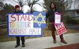 People hold signs of support near the house of Rabbi Chaim Rottenberg on December 29, 2019 in Monsey, New York. (Photo by Kena Betancur / AFP)
