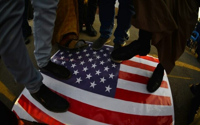 Iraqis step on a US national flag on December 30, 2019, during a demonstration in the holy shrine city of Najaf to denounce the previous night's attacks by US planes on several bases belonging to the Iran-backed Kateb Hezbollah militia. (Haidar HAMDANI/AFP)