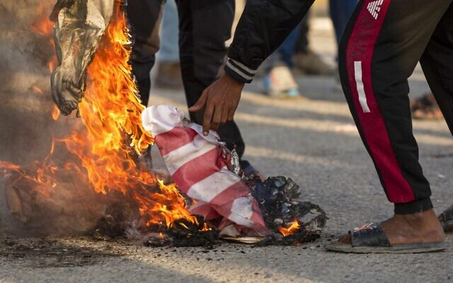 Iraqis burns the American flag in the southern city of Basra on December 30, 2019, during a demonstration to denounce the previous night's attacks by US planes on several bases belonging to Kataeb Hezbollah near Al-Qaim, an Iraqi district bordering Syria. (Hussein FALEH / AFP)
