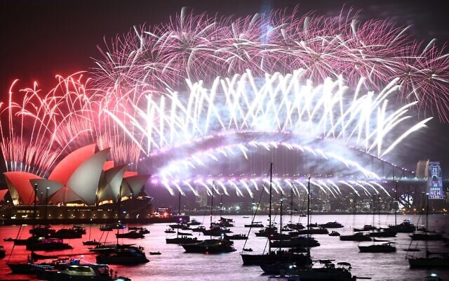 New Year's fireworks erupt over Sydney's iconic Harbour Bridge and Opera House (L) during the fireworks show on January 1, 2020. (Peter Parks/AFP)