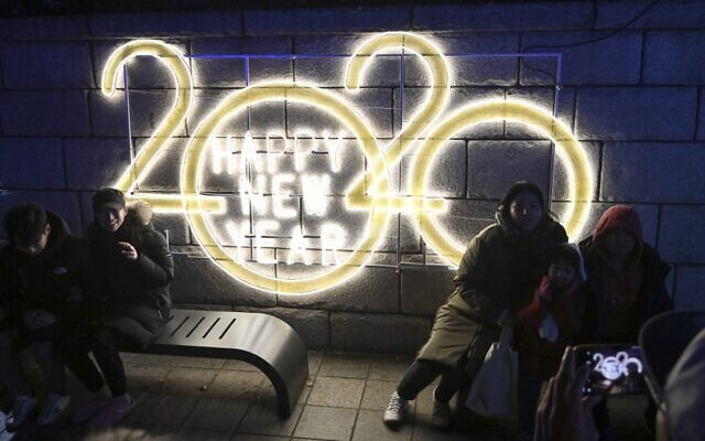 People pose for a picture in front of a 2020 luminous sign after midnight during a countdown event to mark the New Year in central Seoul on January 1, 2020. (Jung Yeon-je/AFP)