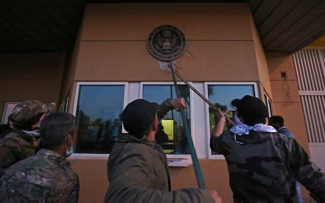 Iraqi supporters and members of the Popular Mobilization Forces paramilitary pull off a plaque from the entrance of the US embassy in Baghdad, Iraq, December 31, 2019. (Ahmad al-Rubaye/AFP)