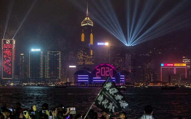 Pro-democracy protesters and revelers gather at the promenade of Tsim Sha Tsui district as fireworks explode over Hong Kong on January 1, 2020. (Philip Fong/AFP)